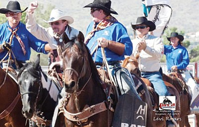 Courtesy<BR> Levi Rogers, at center wearing a white hat, waves to the crowd as he rides in surrounded by supporters during the grand entry at the 29th Annual Andy Devine Days Rodeo. From left are Bill Stinemates, Rogers, Scott Honeycutt, Chas Barker and Janet Honeycutt. Stinemates and the Honeycutts are from Honeycutt Rodeo.