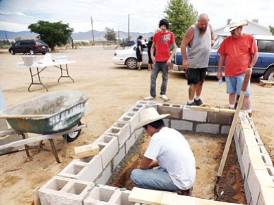 Courtesy<BR>Joseph Songster works on his Eagle Scout project as, from left, Boy Scout John White Jr., project mentor John White Sr. and Songster's father, Robert Songster, watch his progress.