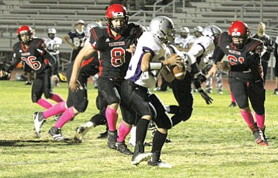 JC AMBERLYN/Miner<BR> Lee Williams High's Dallas Morgan (8) and Kaleb Smith (61) close in on Sedona Red Rock quarterback Derrick Johnson while Andrew Davis (36) follows the action in the Volunteers' 29-14 win Friday at LWHS.