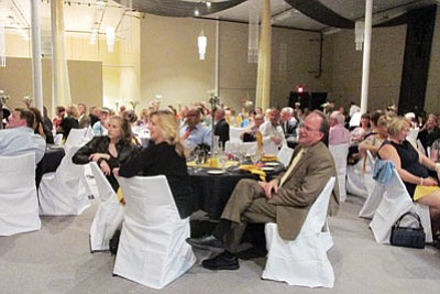 KIM STEELE/Miner<BR> Guests listen during dinner at Beale Celebrations as owner Werner Fleischmann describes his love for Kingman and discusses some of his ongoing projects. Although construction is not complete at the building, it opened to the public Saturday and business is going strong.