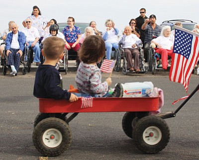 Parade participants from Lilly Pad Daycare wave to the crowd at the 2009 Veteran's Day Parade held at the Lingenfelter Center and The Gardens at Kingman. (JC AMBERLYN/Miner)