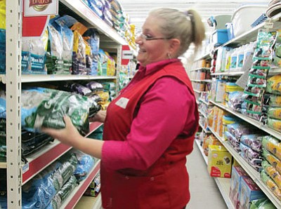 KIM STEELE/Miner<BR> Team leader Ann Marie Borthwick stocks cat food on shelves at the new Tractor Supply Company, which opens Wednesday. The store is located in Frontier Crossing and carries products that help maintain farms, ranches, homes and animals.