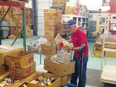 SHAWN BYRNE/Miner<BR> Don Martin, who volunteers at Kingman Area Food Bank, sorts through items on Friday brought to the food bank by 4-H clubs the Wranglers, Thundering Hooves, Fancy Feathers and Furs.