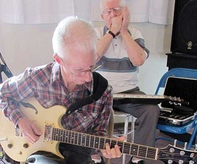 KIM STEELE/Miner<br /><br /><!-- 1upcrlf2 -->Jim Barnes, 72, of First Pentecostal Church of God, strums an electric guitar as Ralph Holt, 89, a member of Church of the Nazarene, plays a harmonica behind him. Holt also played a lap steel guitar.