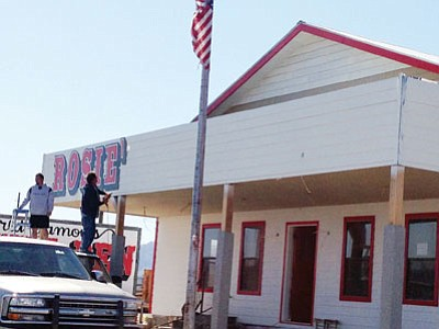 Courtesy<BR> The sign goes up on Rosie's Den, the roadside stop south of Hoover Dam that went up in flames in August 2011.