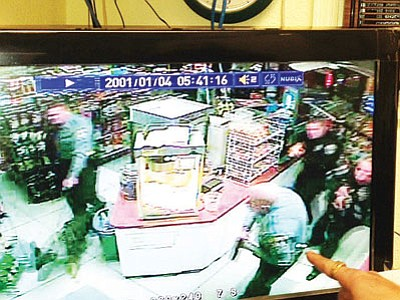 In this screen grab from surveillance video, law enforcement personnel from the Kingman Police Department and Mohave County Sheriff's Office, along with an MCSO K9, approach an alleged burglar with their weapons drawn. A man was hiding in a store's walk-in cooler early Sunday morning, reportedly smoking a cigarette, when he was apprehended. (Courtesy)