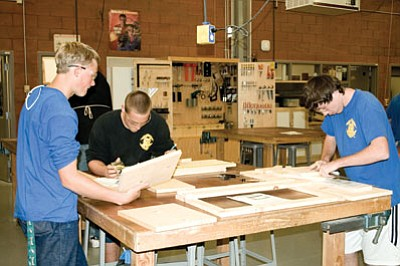 Kingman High School students, from left,  Austin Robinson, Robert Blaze and Isaac Stewart piece together their projects in woodworking class. The class is one of several Career and Technical Education classes offered by the Kingman Unified School District that prepare students for the workplace.  (SUZANNE ADAMS-OCKRASSA/Miner)