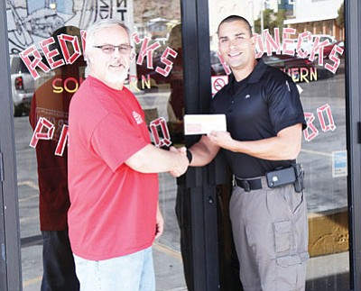 Courtesy<BR>Kingman Police Detective Brian Zach, right, receives gift certificates from Redneck's BBQ owner Bubba Floyd. The certificates are for Thanksgiving dinners that were given to deserving Kingman families.