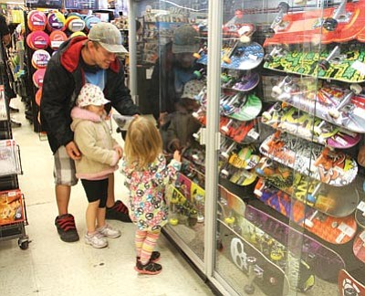 JC AMBERLYN/Miner<BR> Shoppers came out in full force for Black Friday sales in Kingman. From left to right, Mike Wilson, Sunny, 4, and Stormy Waters, 2, look at skateboards while shopping at Hastings Entertainment Friday.