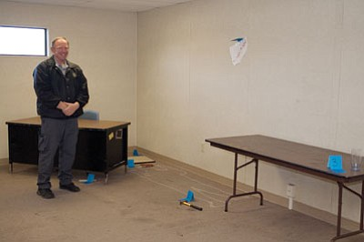 Kerry Schanaman, the Career and Technical Education Law Enforcement teacher for Kingman High School, stands next to a crime scene mock up that his students and students from a social studies class use to study the U.S. criminal justice system. Schanaman was recently awarded a $5,000 grant from the Western Arizona Vocational Education Joint Technical Education District to help cover the cost of a machine that will analyze DNA. (SUZANNE ADAMS-OCKRASSA/Miner)