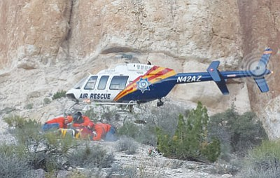 Members of Mohave County Search and Rescue units prepare an injured patient for transport as a Department of Public Safety Air Ranger crew lands in rugged terrain Saturday. (BUTCH MERIWETHER/Courtesy)<br /><br /><!-- 1upcrlf2 -->