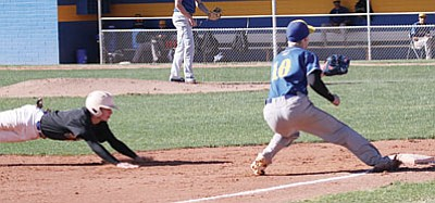 JC AMBERLYN/Miner<BR> Kingman Academy's Westin McCord dives into third base as Kingman's Joey Scott readies to take the throw during Kingman Academy's 13-10 win Tuesday at KHS.