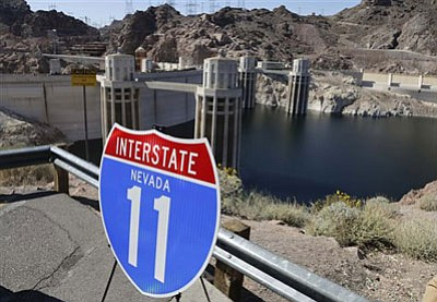 A sign that will mark the proposed corridor of Interstate 11 between Phoenix and Las Vegas sits on the edge of a parking lot overlooking Hoover Dam, Friday, March 21, 2014, at Hoover Dam, Ariz. Arizona governor Jan Brewer and Nevada governor Brian Sandoval gathered to unveil signs in a symbolic effort meant to keep up momentum on the project, which is coming of age in an era of scarce highway funding. <i>(AP Photo/Julie Jacobson)</i>