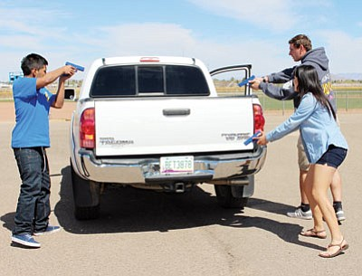 From left, Kingman High School seniors Jonathan Delgado, 17, Selena Leon-Vega, 18, and Joseph Beale, 18, hold Glock 9mm training replicas on a suspect in a truck during a practice felony traffic stop on school property. The students are part of the Forensic Law Enforcement Program. (KIM STEELE/Miner)