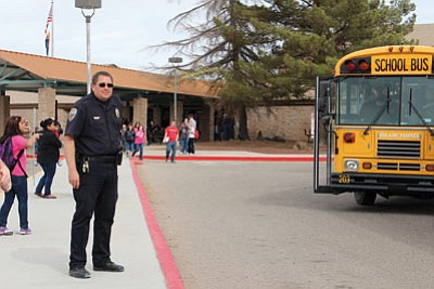 RYAN ABELLA/Miner<BR> A Kingman Police officer keeps an eye on the neighborhood as Hualapai Elementary School is dismissed Friday afternoon during a manhunt.