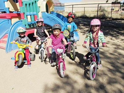 From left, Alex Grant, Althea Watkins, Trinity Mclaughlin, David Bravo and Sheila Hilderbrand practice riding-toy safety by wearing their helmets. They will be participating in the St. Jude Trike-A-Thon this week. (KIM STEELE/Miner)