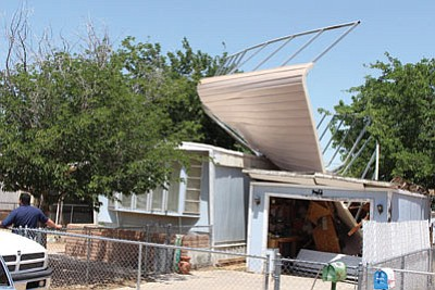 An unsecured carport crashed atop Delmar and Phyllis Suttons' home on John L Avenue Thursday night, and remains there nearly four days later. (MATT REINIG/Miner)