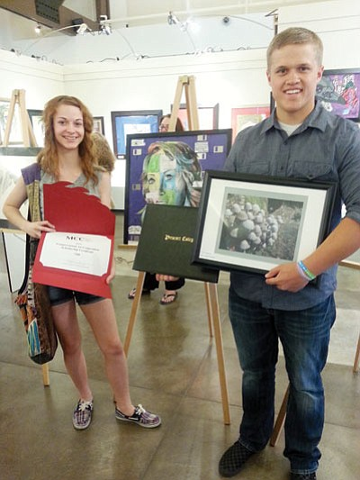 Kingman Academy High School students Samantha Rezzetti and Samuel Block show off the artwork they created and scholarships they won as part of the 2014 Congressional Art Competition, sponsored by U.S. Rep. Paul Gosar, R-Ariz., earlier this month. (Courtesy)