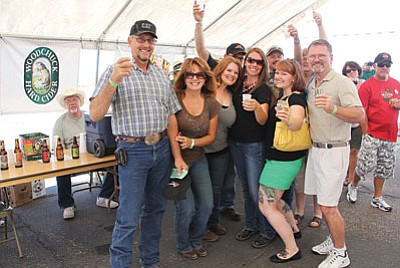 People raise a glass and smile at the Mohave County Fair Association's inaugural Beerfest at the Mohave County Fairgrounds last year.