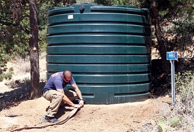 JC AMBERLYN/Miner<BR> Firefighter Mike Schmidt attaches the hose to water tank #3 Friday in the community of Pinion Pine.