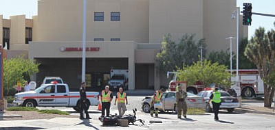 Kingman police and firefighters clean up an accident scene Friday. A motorcyclist went to a Las Vegas hospital with serious injuries. (KIM STEELE0Miner)