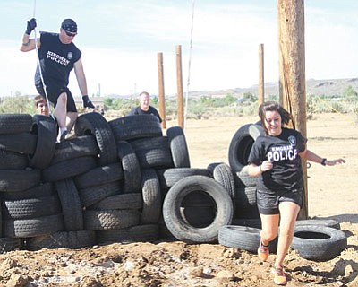 The Kingman Police Department team is shown making their way through the course. From left to right are (cresting the tires) Dennis Miller, Robert Trujillo, Matt Snay and Amber Quintanilla.(JC AMBERLYN/Miner)