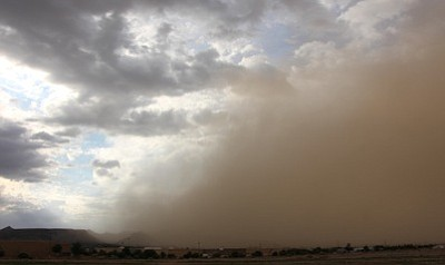 A cloud of dust moved across Kingman Sunday evening, reducing visibility and turning the sky burnt orange. (ALAN CHOATE/Miner)