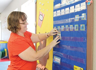 KIM STEELE/Miner<BR> AmySue Crawford, a kindergarten teacher at Emmanuel Christian Academy, readies her room for the first day of school on Aug. 11. Crawford is entering her second year of teaching at the private religious school.