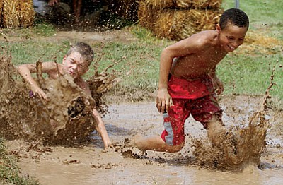 JC AMBERLYN/Miner<BR>James Wilson, 9 (left), and Keygun Field, 8, race in the mud.