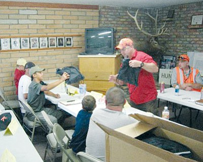 Courtesy<BR> Shane Vernon of Nucor Steel passes out gift bags of safety items to members of hunter education class  R-2-2014 on Sunday. Looking on is Instructor Johnnie Hoeft. For more on Nucor's special relationship with hunt education, see Page 18.