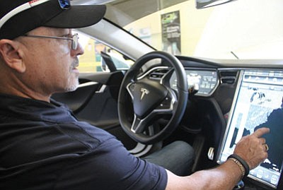 Tudor Melville shows off some of the features of his 2013 Tesla Model S. (JC AMBERLYN/Miner)