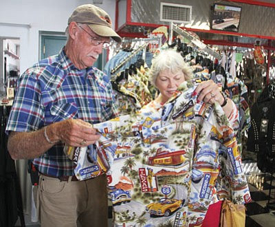 Charlie and Paula Johnson of Santa Barbara, Calif., look over a shirt with scenes representing well-known locations along Route 66 at the Memory Lane Gift Shop on Thursday. (JC AMBERLYN/Miner)
