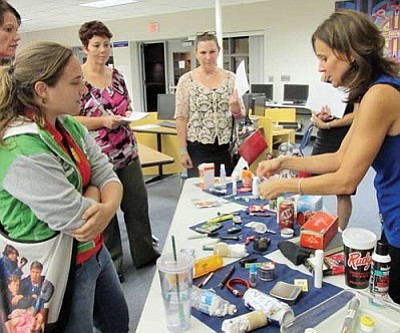 KIM STEELE/Miner<br /><br /><!-- 1upcrlf2 -->Participants in a Current Drug Trends and Identification seminar at Kingman High School view some of the gadgets teenagers use to smoke, take and hide illegal and prescription drugs as speaker Debi LaVergne demonstrates one.