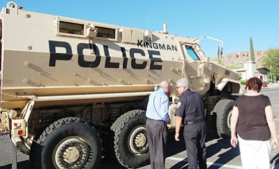 Police Chief Robert DeVries discusses the department's newly repurposed armored vehicle prior to Tuesday's City Council meeting as Mayor Janet Watson continues her review. The Department of Defense gave the $750,000 vehicle to the KPD at no charge. The money used to ship it from Texas and outfit it came from drug forfeiture money. (DOUG McMURDO/Miner)