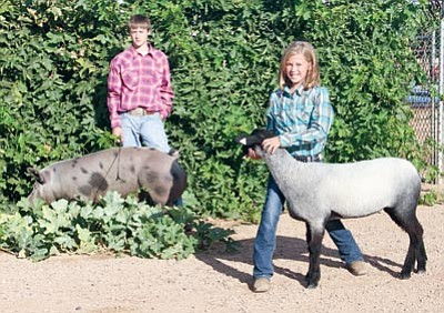 JC AMBERLYN/Miner<BR> Sid Jensen, with male spot cross pig Digger, and Ashlee Steele with Daisy, a Suffolk/Hampshire cross female sheep.