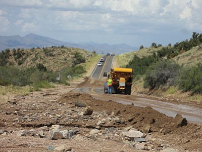 A plow truck clears Hualapai Mountain Road at mile marker 5 Sunday following heavy rains. (ROSCOE GRAY/Courtesy)