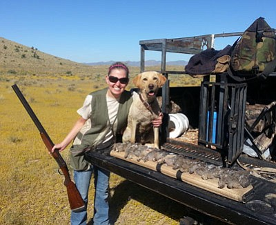 Courtesy<BR> Lacie Robbins poses with Stella, a yellow Labrador retriever, as she shows the limit of mourning doves she bagged near Kingman on her first dove hunt.