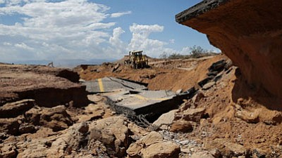 A bulldozer works on a flood damaged area of Interstate 15, Tuesday, Sept. 9, 2014, near Moapa, Nev. Flood damage caused the closure of the interstate which is the main road between Las Vegas and Salt Lake City. (AP Photo/John Locher)