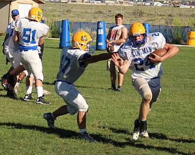 Kingman quarterback Daniel Williford avoids John Redding's tackle during practice last week. The Bulldogs host Goldwater in their home opener at 7 p.m. today.
