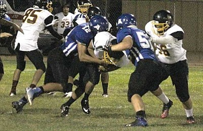 Tristen Pitts (12) and Sam Block (52) take down an ASU Prep ball carrier for Kingman Academy last week. Tackling will be key if the Tigers hope to upset Yuma Catholic tonight.
