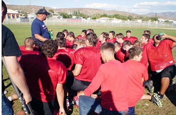 Lee Williams High School defensive coordinator Joe Juelfs talks things over with his players during practice. The Volunteers take on the No.-1 ranked River Valley Dust Devils Friday at Mohave Valley.
