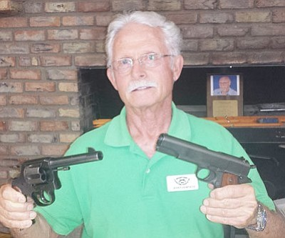 DON MARTIN/For the Miner<br /><br /><!-- 1upcrlf2 -->Mohave Arms Collector president Jerry Haworth holds a .45-caliber revolver and a .45-caliber semi-automatic pistol. Both were manufactured during World War I. <br /><br /><!-- 1upcrlf2 -->