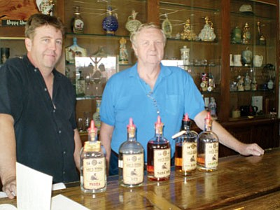 HUBBLE RAY SMITH/Miner<BR> John Patt and his father, Peter, owners of Desert Diamond Distillery in Kingman, display some of their spirits on the tasting bar at their distillery. A new law allows them to sell their spirits at other venues. See more on 5.