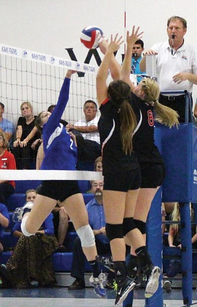 SHAWN BYRNE/Miner<BR> Lee Williams' Marli Lauck, left, and Sadie Snay (8) go up to block Academy's Kiersten Kinsey's kill attempt Sept. 11 at Kingman Academy.
