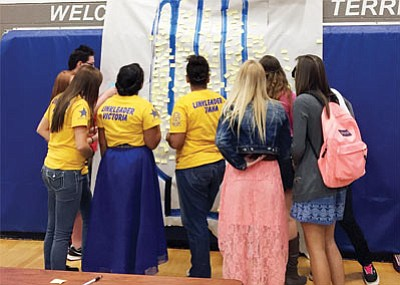 "Students at Kingman High School gather around a giant hand symbolizing the challenge ""Take a stand, lend a hand"" and attach sticky notes with their commitment to stop bullying. Some of the notes read ""Respect,"" ""Speak up and help them,"" ""Pray,"" ""Don't be a bystander,"" ""Help"" and ""Tell someone."" (Courtesy)"