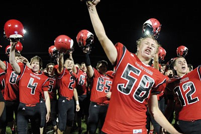 ALAN CHOATE/Miner<BR> Lee Williams' Tim Lutz (58) leads the celebration of Friday's overtime win over Kingman Academy, but the Tigers also qualified for the playoffs after a number of other teams in the mix fell by the wayside. LWHS enters as the No. 12 seed, KAHS as the No. 15.