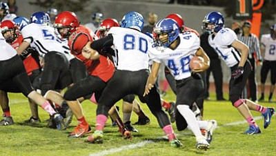 ALAN CHOATE/Miner<BR> Kingman Academy running back Jordan McDowell-Seybert (48) sees daylight around the block of Breyden Potter (80) against Lee Williams High School Friday night. McDowell-Seybert led the Tigers with 39 yards rushing on eight carries.