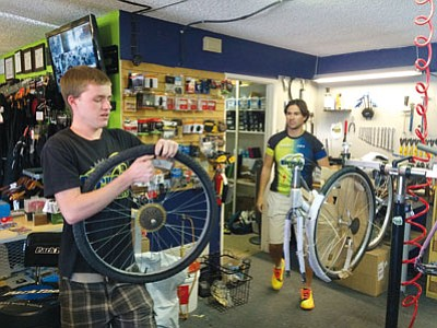 HUBBLE RAY SMITH/Miner<BR> Kyle Burchard works on a bicycle tire at Bicycle Outfitters Kingman while shop owner Adolfo Rodriguez watches. They both competed in the Kingman Rattler mountain bike race Sunday at Monolith Gardens. The race was sponsored by the Colorado River Area Trail Alliance.