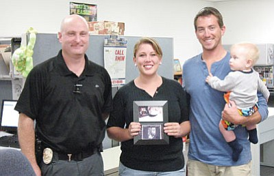 Kingman Police Detective Todd Foster, left, presented Dominie and Brent Green, along with baby Jeremiah, with important family photographs and video that was on a camera a thief stole last spring. (Courtesy)