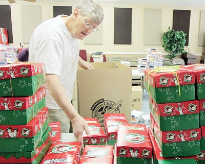 Mike Baldwin, Mohave County collection coordinator for Operation Christmas Child, packs shoeboxes filled with goodies that will be sent overseas to needy children. (KIM STEELE/Miner)